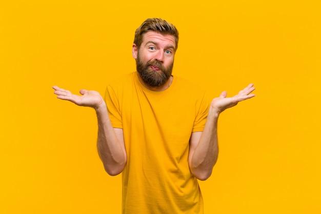 Giovane uomo biondo sentirsi perplesso e confuso, dubitando, ponderando o scegliendo diverse opzioni con espressione divertente sulla parete arancione