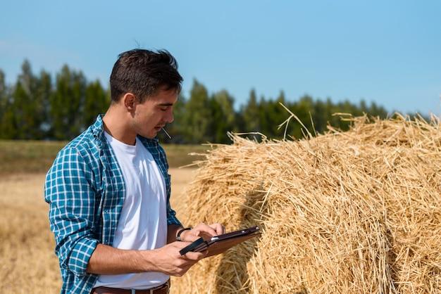 Giovane uomo botanico con tavoletta stima il raccolto di fieno