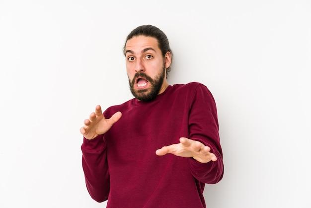 Giovane uomo capelli lunghi isolato su bianco essere scioccato a causa di un pericolo imminente