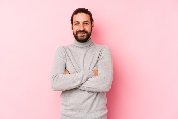 Giovane uomo capelli lunghi isolato su una parete rosa che si sente sicuro di sé, incrociando le braccia con determinazione