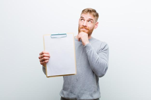 Giovane uomo capo rosso che mostra un documento