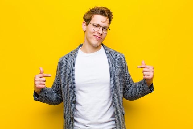 Giovane uomo capo rosso che sembra fiero, positivo e casuale che indica il petto con entrambe le mani arancio