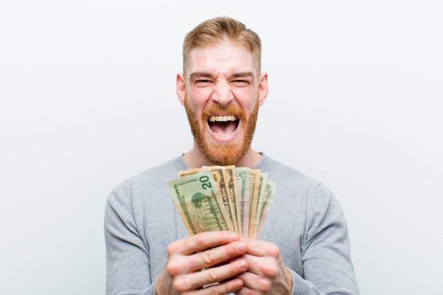 Giovane uomo capo rosso con i dollari contro fondo bianco
