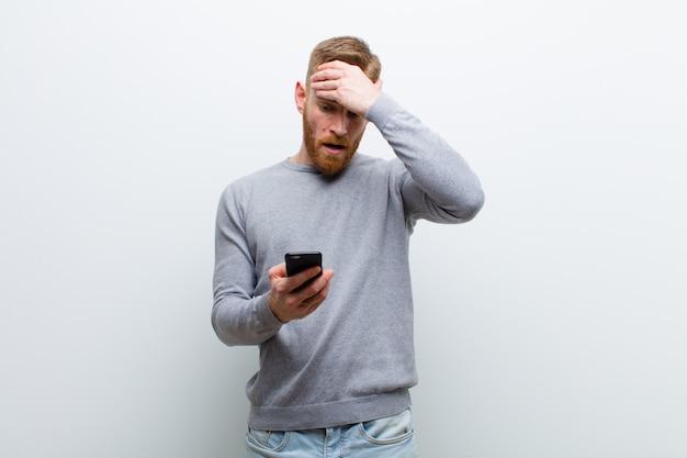 Giovane uomo capo rosso con uno smart phone su sfondo bianco