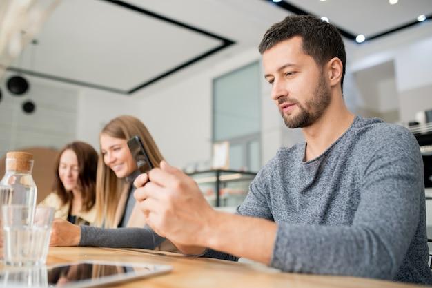 Giovane uomo casual guardando lo schermo dello smartphone mentre fa selfie o comunica con qualcuno con due ragazze