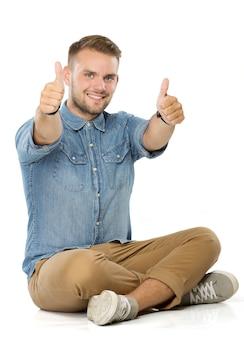 Giovane uomo casual seduto con le gambe incrociate e mostrando entrambi i pollici