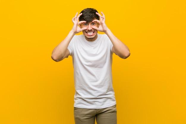 Giovane uomo casual tenendo gli occhi aperti per trovare un'opportunità di successo