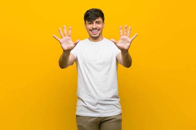 Giovane uomo casuale ispanico che mostra numero dieci con le mani.