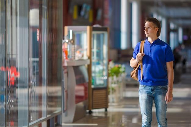 Giovane uomo caucasico all'imbarco aspettante dell'interno dell'aeroporto