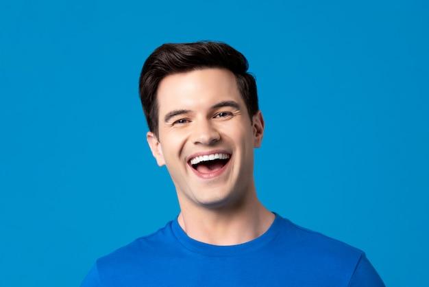 Giovane uomo caucasico amichevole in semplice t-shirt blu ridendo
