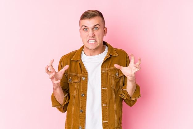 Giovane uomo caucasico arrabbiato che grida con le mani tese.