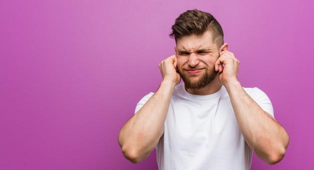Giovane uomo caucasico bello che copre le orecchie con le sue mani.