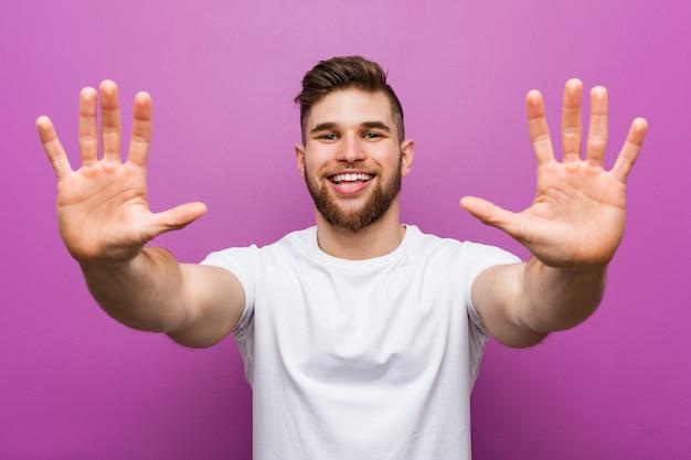 Giovane uomo caucasico bello che mostra numero dieci con le mani.