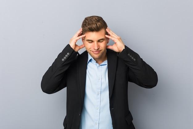 Giovane uomo caucasico bello che tocca le tempie e che ha mal di testa.