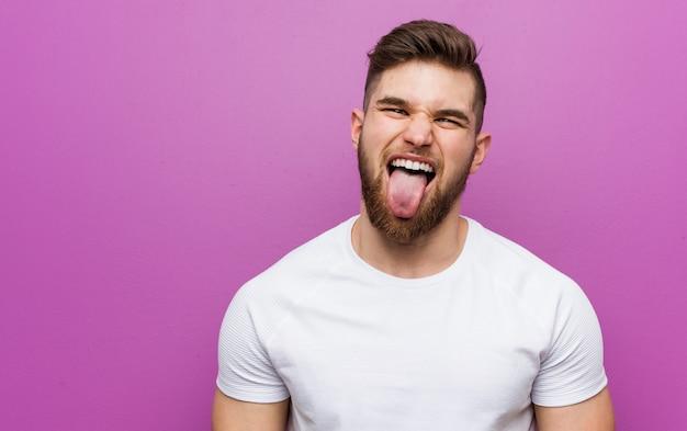 Giovane uomo caucasico bello divertente e amichevole che attacca fuori la lingua.