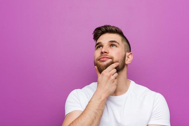 Giovane uomo caucasico bello lateralmente con espressione dubbiosa e scettica.