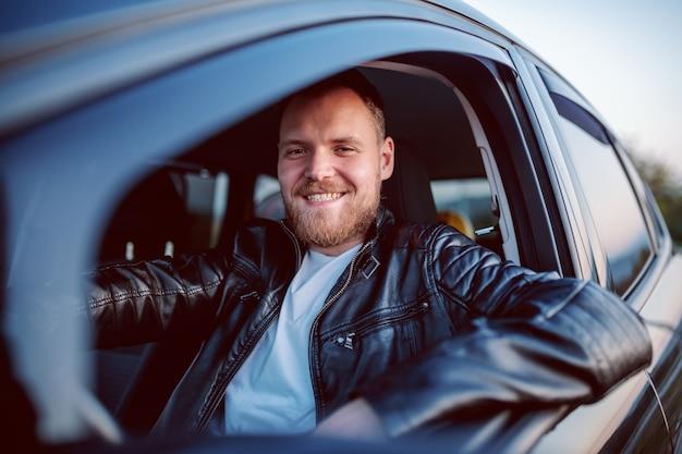 Giovane uomo caucasico biondo barbuto sorridente bello in giacca di pelle in posa nella sua automobile moderna.