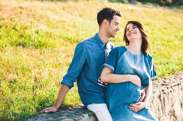 Giovane uomo caucasico che abbraccia moglie incinta
