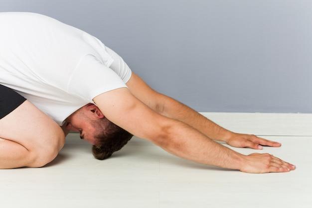 Giovane uomo caucasico che allunga yoga di pratica