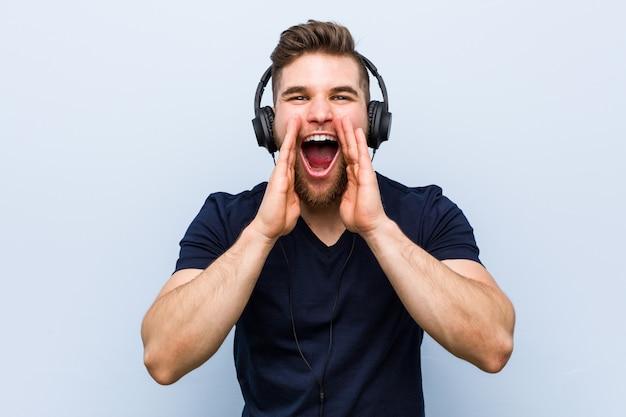 Giovane uomo caucasico che ascolta la musica che grida eccitato alla parte anteriore.