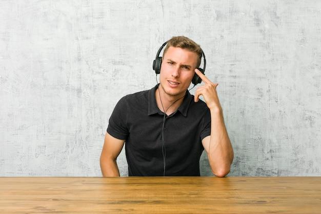 Giovane uomo caucasico che ascolta la musica con le cuffie che mostrano un gesto di delusione con l'indice.