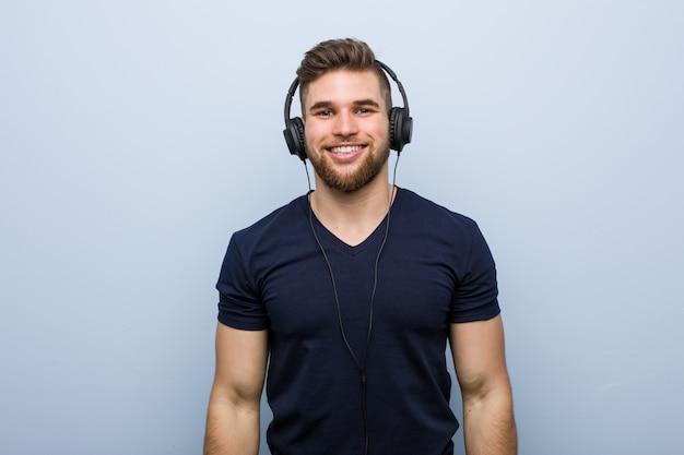 Giovane uomo caucasico che ascolta la musica felice, sorridente e allegra.