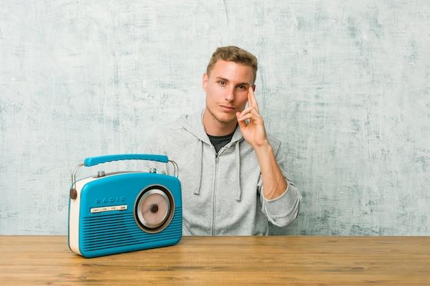Giovane uomo caucasico che ascolta la radio che indica tempio con il dito