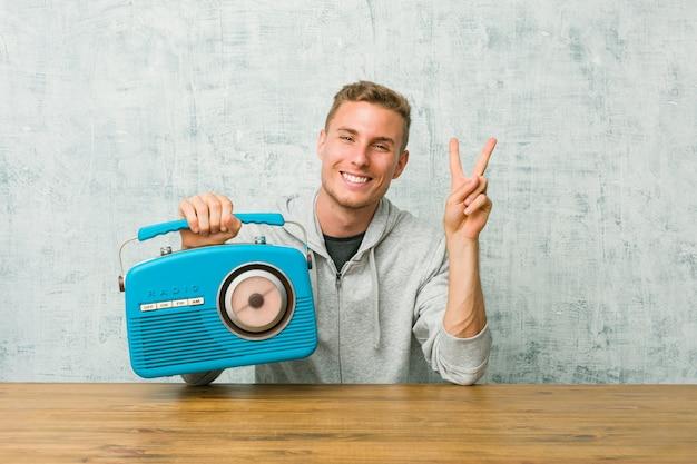 Giovane uomo caucasico che ascolta la radio che mostra il segno di vittoria e che sorride ampiamente.