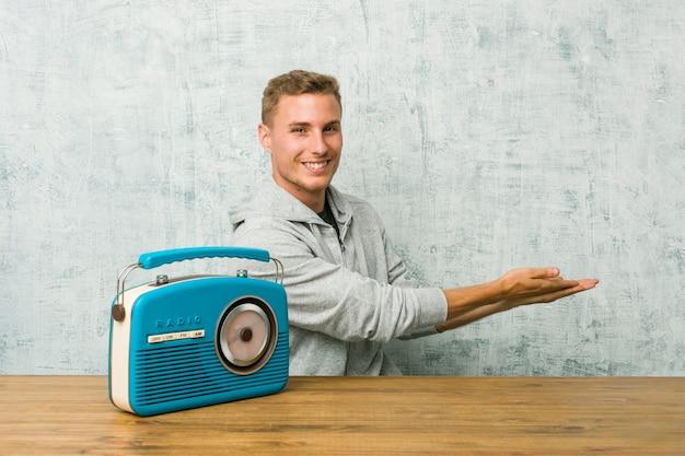 Giovane uomo caucasico che ascolta la radio che tiene uno spazio della copia su una palma