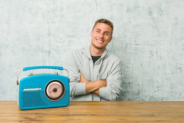 Giovane uomo caucasico che ascolta la radio sorridente fiducioso con le braccia incrociate.