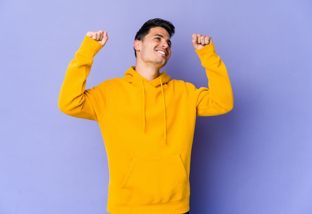 Giovane uomo caucasico che celebra un giorno speciale, salta e alza le braccia con energia.