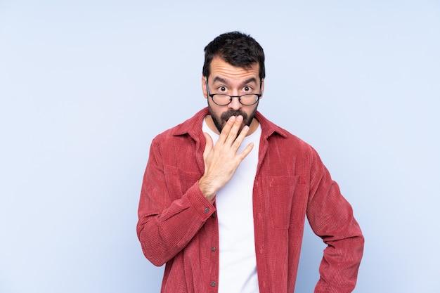 Giovane uomo caucasico che indossa giacca di velluto a coste sulla parete blu con gli occhiali e sorpreso