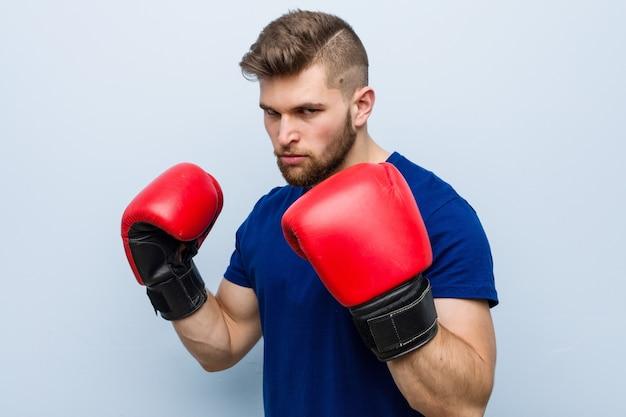 Giovane uomo caucasico che indossa guantoni da boxe