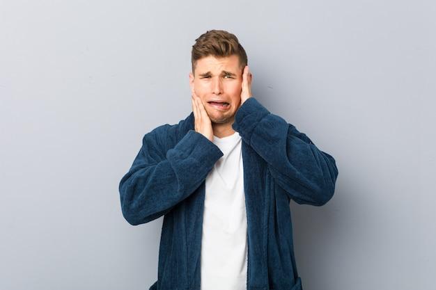 Giovane uomo caucasico che indossa pigiama piagnucolando e piangendo sconsolato.