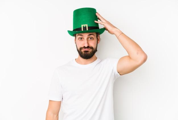 Giovane uomo caucasico che indossa un cappello di san patrizio isolato essendo scioccato, ha ricordato un incontro importante.