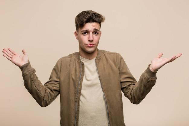 Giovane uomo caucasico che indossa una giacca marrone dubitando e scrollando le spalle le spalle in gesto interrogativo.