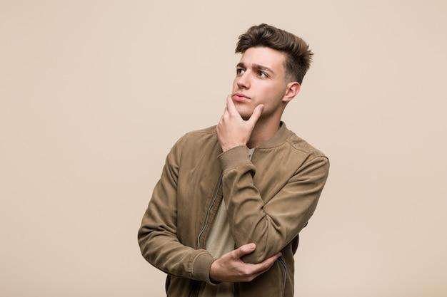 Giovane uomo caucasico che indossa una giacca marrone guardando lateralmente con espressione dubbiosa e scettica.