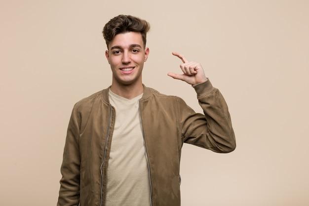 Giovane uomo caucasico che indossa una giacca marrone in possesso di qualcosa di piccolo con gli indici, sorridente e fiducioso.