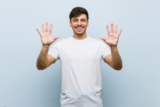 Giovane uomo caucasico che indossa una maglietta bianca che mostra il numero dieci con le mani.