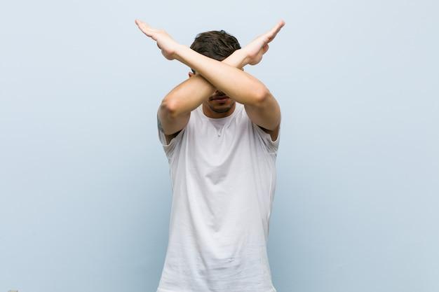 Giovane uomo caucasico che indossa una maglietta bianca mantenendo due braccia incrociate, concetto di rifiuto.