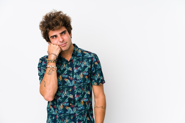 Giovane uomo caucasico che indossa una maglietta di fiori che si sente triste e pensieroso, guardando uno spazio vuoto.