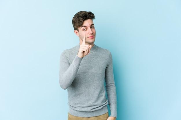 Giovane uomo caucasico che mostra il numero uno con il dito.