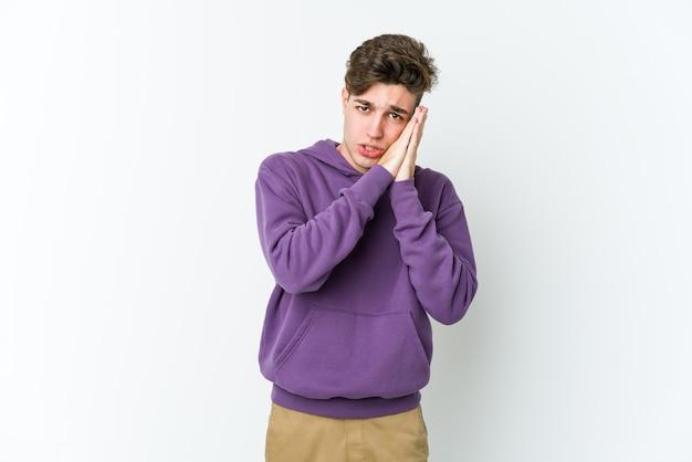 Giovane uomo caucasico che sbadiglia mostrando un gesto stanco che copre la bocca con la mano.