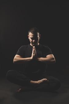 Giovane uomo caucasico che si siede con le mani nel gesto del namaste con i vestiti neri e il nero