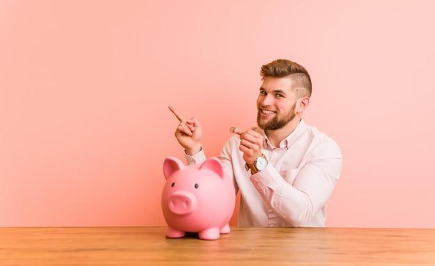 Giovane uomo caucasico che si siede con un porcellino salvadanaio che sorride allegramente indicando con l'indice via.