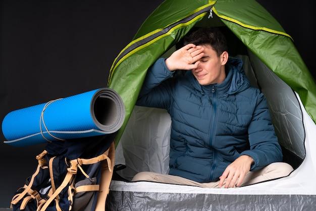 Giovane uomo caucasico che si siede dentro una tenda del riparo