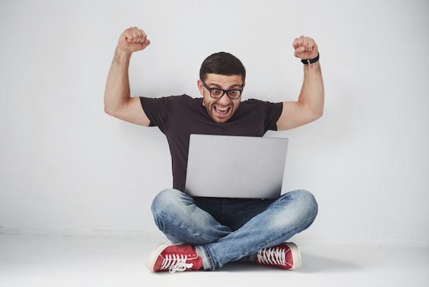 Giovane uomo caucasico che si siede sopra il muro di mattoni bianco facendo uso del computer portatile