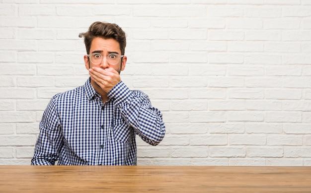 Giovane uomo caucasico che si siede sulla bocca, simbolo di silenzio e repressione, cercando di non dire nulla