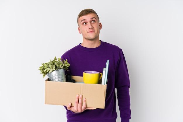 Giovane uomo caucasico che si trasferisce in una nuova casa sognando di raggiungere obiettivi e scopi