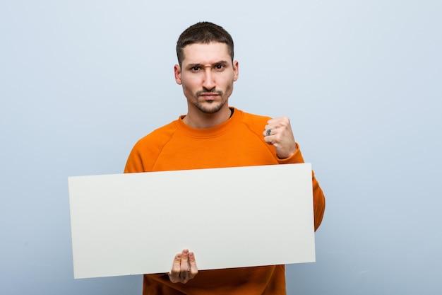 Giovane uomo caucasico che tiene un cartello che mostra pugno, espressione facciale aggressiva.